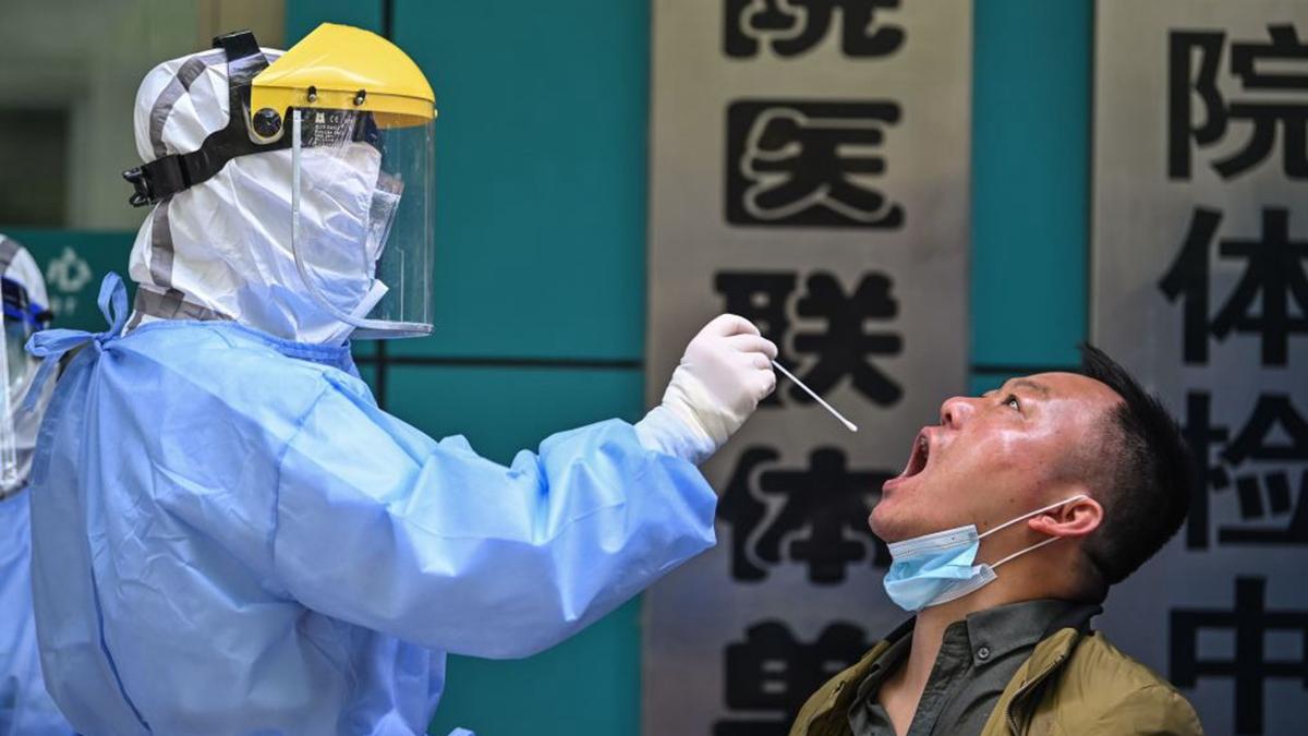 圖為2020年4月16日,武漢醫護人員在給市民採集口腔樣本。(HECTOR RETAMAL/AFP via Getty Images)