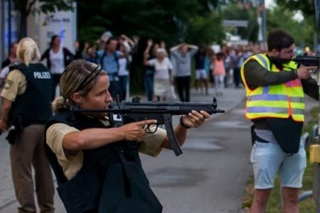 7月22日,德國慕尼黑驚傳槍擊,10人死亡,27人受傷,年僅18歲的伊朗裔德國籍槍手隨後自盡。圖為警方持槍護送民眾撤離。(Joerg Koch/Getty Images)