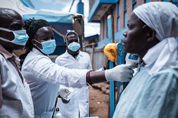 3月18日內羅畢,一個非政府組織工作人員在給一名婦女測體溫。(YASUYOSHI CHIBA/AFP via Getty Images)