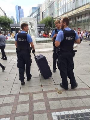 三名配槍警察將一個無主的行李箱拉走檢查。(文婧/大紀元)