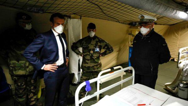 3月25日,馬克龍(中)探視收治感染中共病毒患者的野戰醫院。(MATHIEU CUGNOT/POOL/AFP via Getty Images)