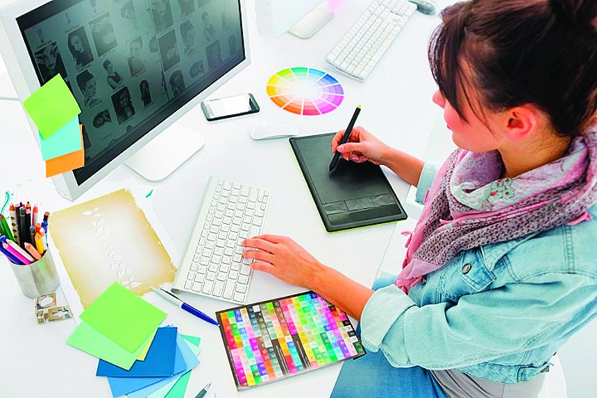 藝術家在辦公室的平板電腦上繪製東西的高角度視圖。