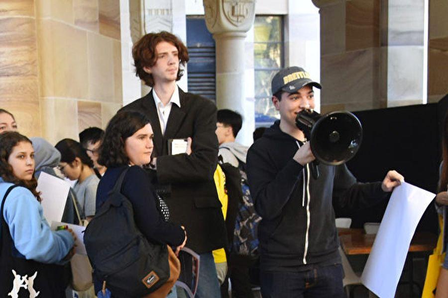 昆士蘭大學學生帕夫洛(Drew Pavlou)(右邊手持喇叭者)近日表示,自己將被大學開除,他認為這或許與他狀告布里斯本中領館領事徐傑有關。(楊裔飛/大紀元)