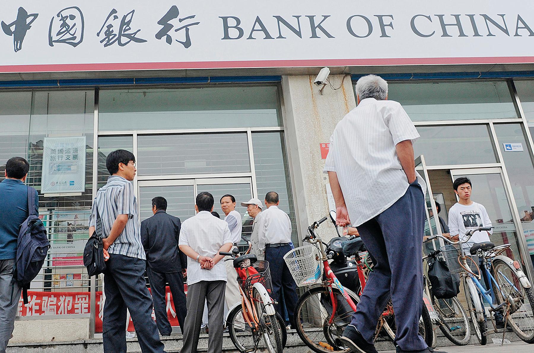 國際石油期貨震盪令中國銀行原油寶投資者,一夜間背負巨額虧損。圖為 2010 年人們在中國銀行門外排隊。(AFP)