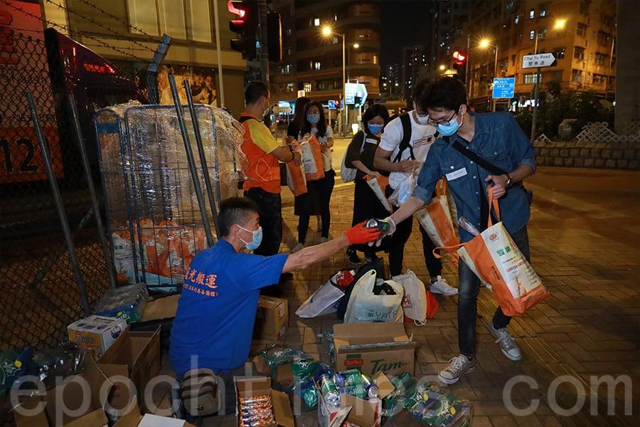 一眾義工有序地包裝約一百袋「防疫福袋」。(陳仲明/大紀元)