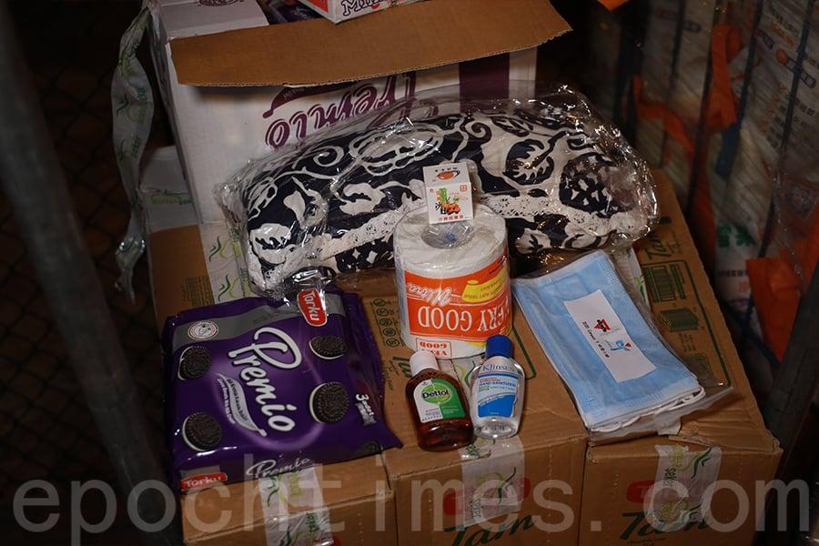 防疫福袋內有餅乾、飲品、紙巾、日用品、防蚊枕頭等等。(陳仲明/大紀元)