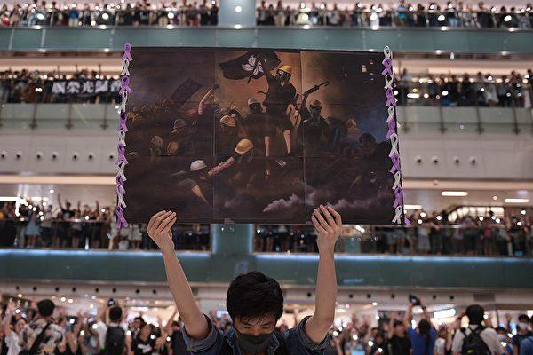 2019年9月11日,在香港沙田區的購物中心裡,一名男子手持反送中海報。這是法新社記者阿斯弗里獲得2020年世界新聞攝影大賽一般新聞類故事組首獎的系列照片之一。(AFP)