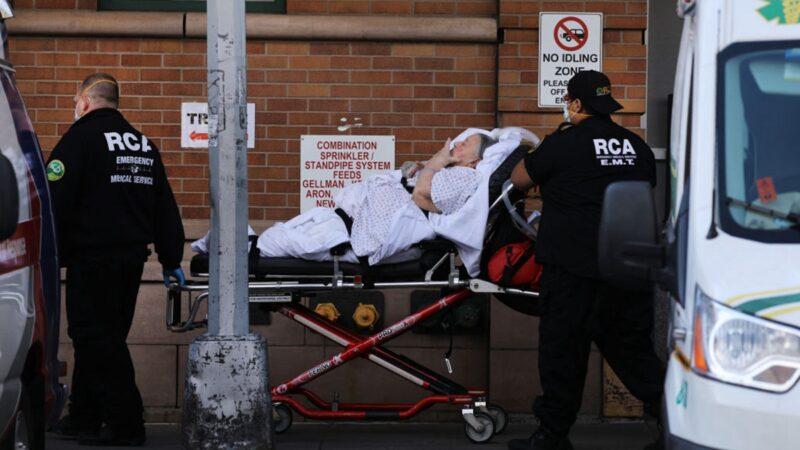 圖為美國紐約警察將患者送入醫院。(Spencer Platt/Getty Images)