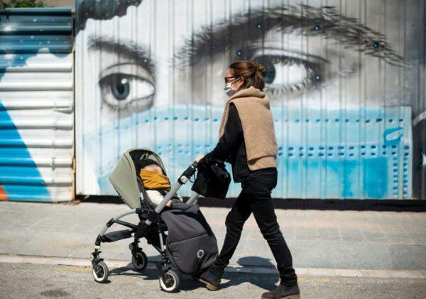 2020年4月26日,西班牙在禁足6周後終解禁,民眾推著嬰兒車走過一幅描繪戴著口罩的人的壁畫。(JOSEP LAGO/AFP via Getty Images)