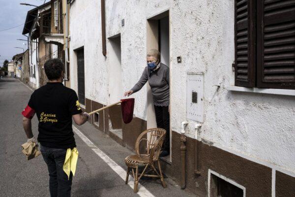 2020年4月26日,意大利北部韋爾切利工作人員分發麵包給一名婦女。(MARCO BERTORELLO/AFP via Getty Images)