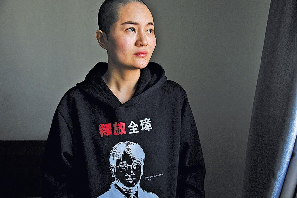 王全璋被捕多年沒有音訊,李文足四處奔走尋找他,她一度剃去長髮向當局抗議。圖為李文足穿著印有丈夫頭像的外套,要求當局釋放他。(AFP)