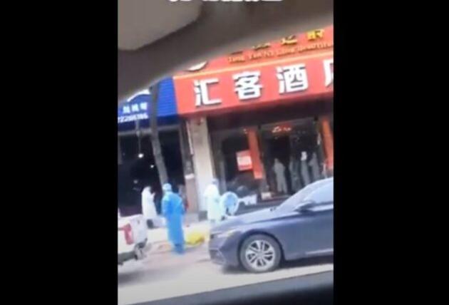 廣州匯客酒店門前的地上放著至少一個黃色疑似運屍袋物品。(影片截圖)