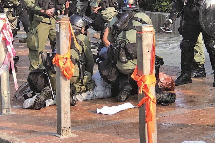 2019年10月27日,市民從尖沙咀梳士巴利花園遊行,追究警方使用暴力。圖 為多位警察圍毆一名抗爭者至昏迷。當日陶輝負責指揮。( 大紀元資料圖片)