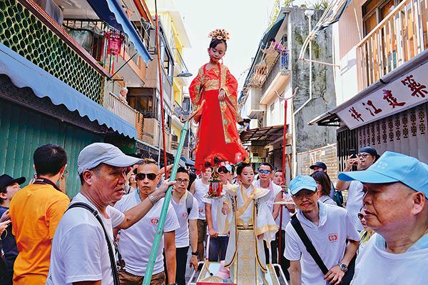 飄色巡遊其中一個特色是讓小孩扮演不同角色,站在架上,由成年人抬高巡遊。(宋碧龍/大紀元)