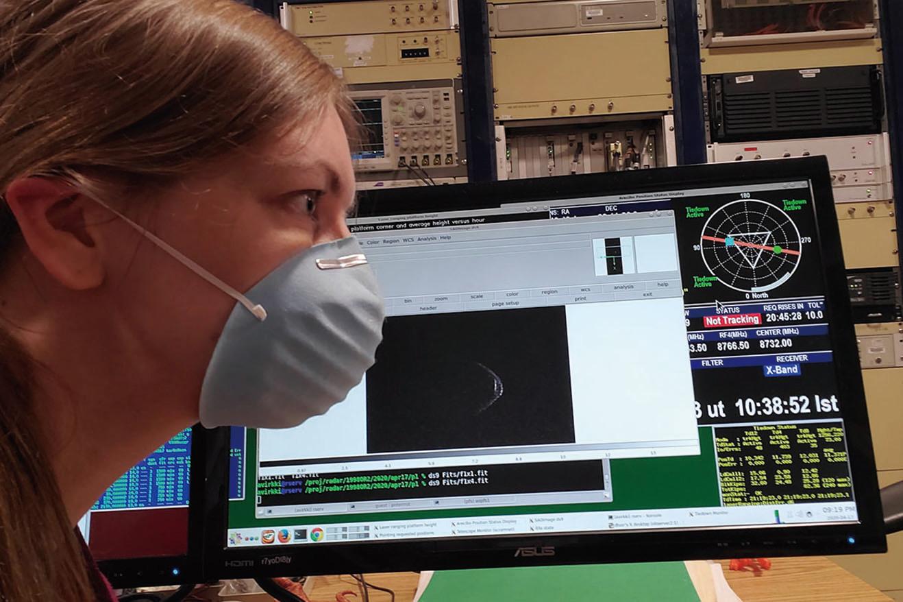 美國阿雷西博天文台行星雷達部門主管維爾基(Anne Virkki)戴著口罩,其身旁雷達畫面顯示的1998 OR2小行星似乎也戴著口罩。(Arecibo Observatory)