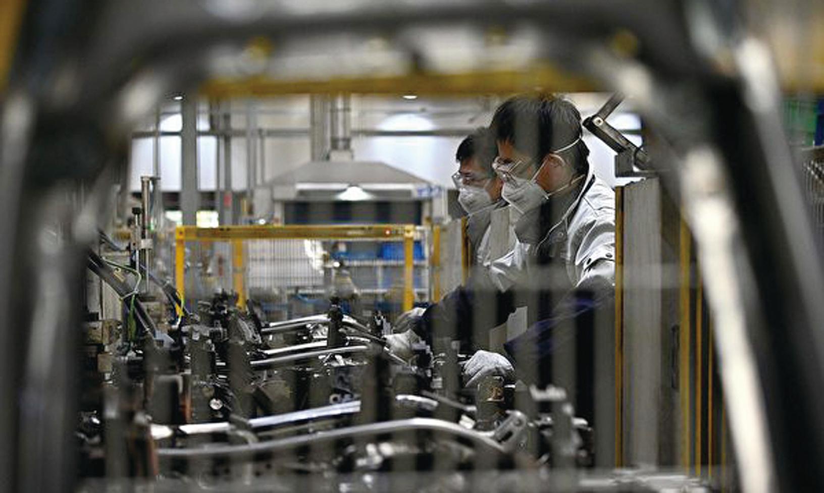 今年中共肺炎疫情爆發,多家中共國企已經或計劃從港交所退市。圖為受疫情影響下的中國工廠。(NOEL CELISAFP via Getty Images)
