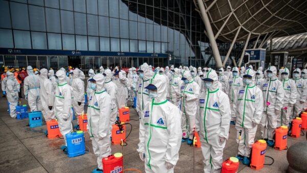 圖為武漢市防疫人員排隊等候噴灑消毒劑。(STR/AFP via Getty Images)