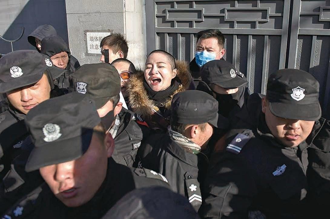 2019年12月28日,稍早以剃髮表達抗議的709案家屬李文足(中,王全璋律師之妻)、王峭嶺(李和平律師之妻)等到北京最高法院遞交「督促函」,要求糾正天津法院就王全璋案「嚴重超出辦案期限」一事等。但受到警察和保安重重阻攔,未能進入法院。(AFP)