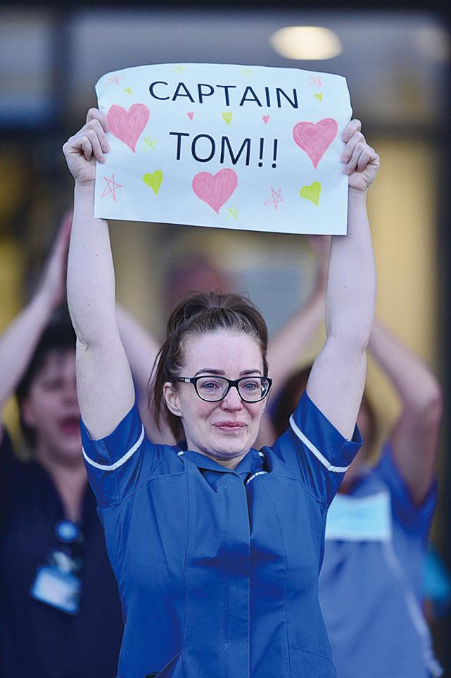 2020年4月16日,英國醫護人員手持標語感謝穆爾為他們募款。(ANTHONY DEVLIN/AFP via Getty Images)