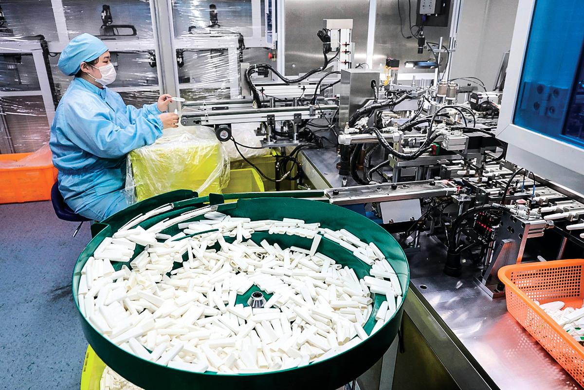 江蘇一家公司的工人在生產病毒檢測盒。(STR/AFP)