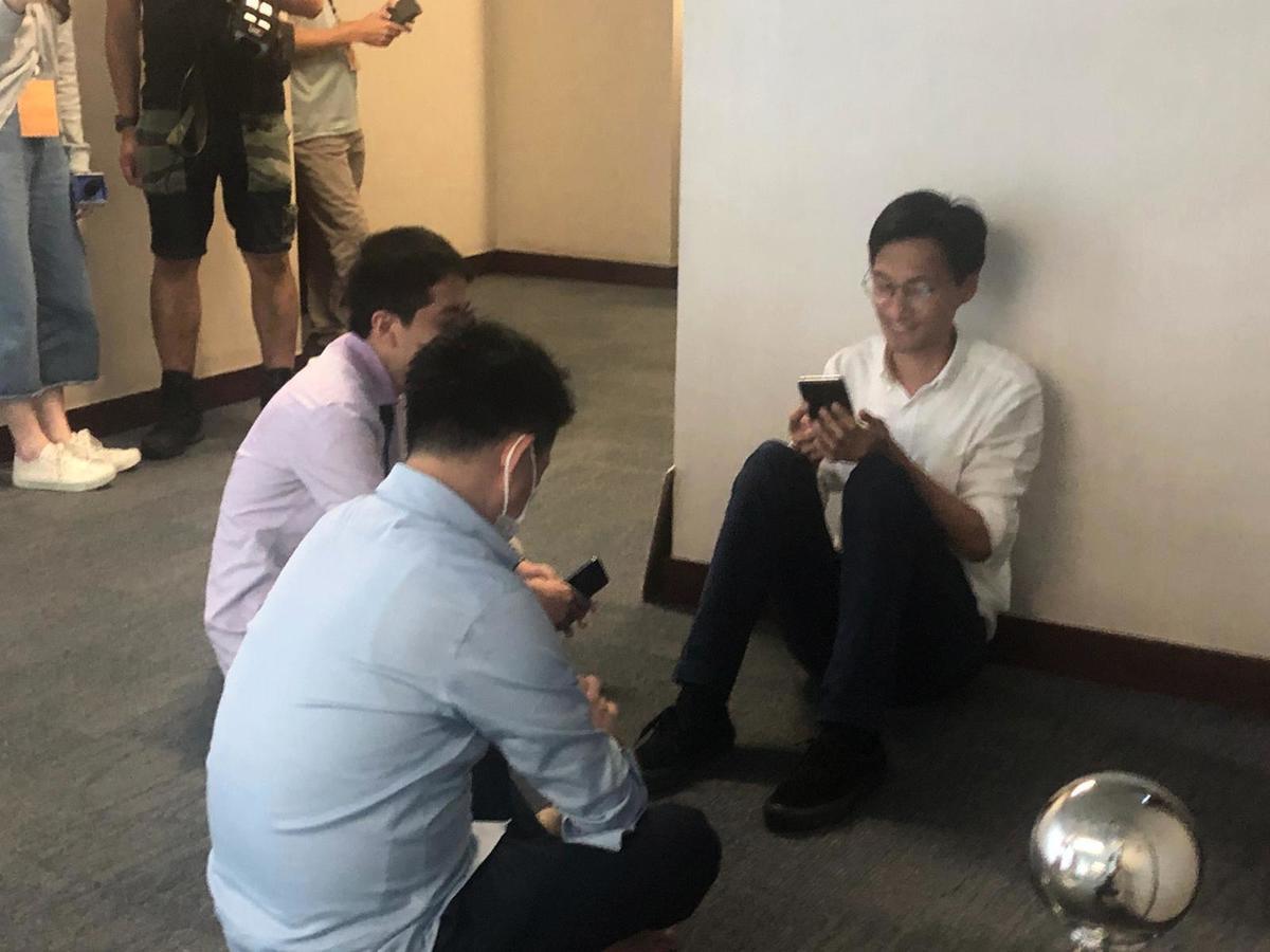 經過一場混亂後,3位被趕出的民主派議員:許智峯、朱凱迪、陳志全,在會議廳外席地而坐,稍作休息 (梁珍 / 大紀元)