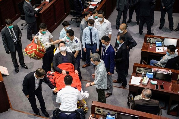 議員尹兆堅疑似受傷,被抬上擔架送醫。(ANTHONY WALLACE/AFP via Getty Images)