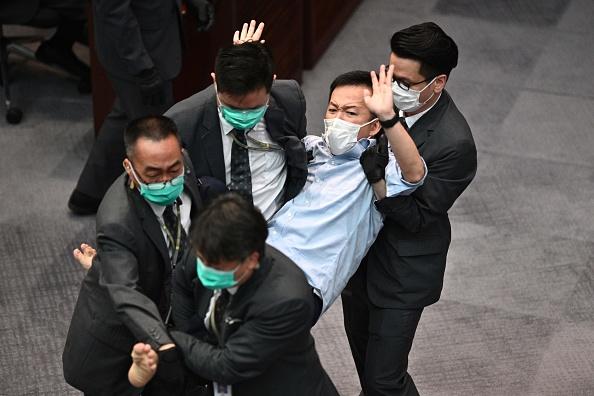 有議員被抬離會議室。(ANTHONY WALLACE/AFP via Getty Images)