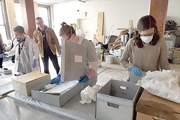 今年1月23日晚間,美國華人博物館藏品倉庫遭遇大火,館內約8.5萬件文物和藝術品或被嚴重損燬。圖為大火撲滅後,義工將箱中的文件取出,確認損毀情況後,再放到暫存文件箱中。(陳家齡提供)