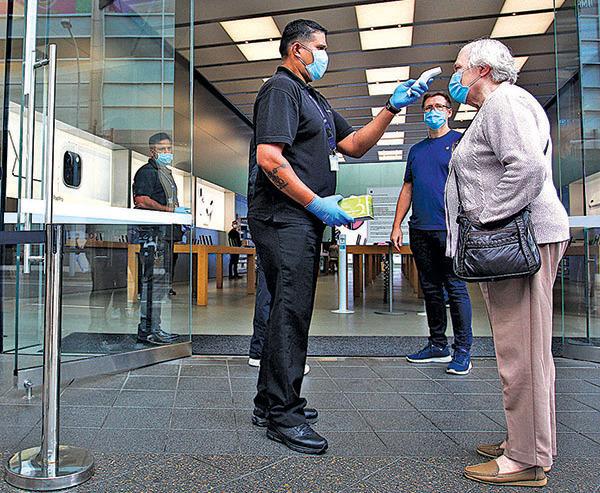 蘋果公司已重開澳洲的部份門店。圖為5月7 日,悉尼一名顧客在進店前接受體溫測試。(Getty Images)