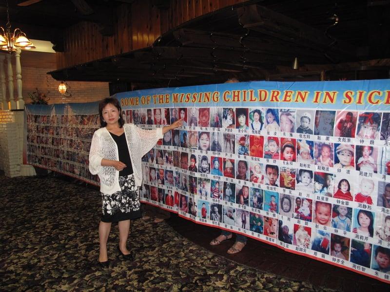 站在數百個中國失踪兒童圖片前的張菁。 (劉菲/大紀元)
