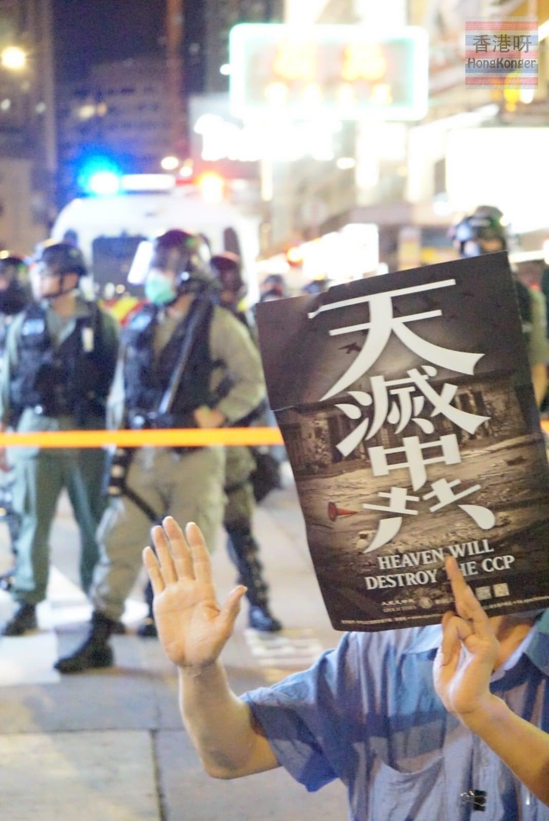 一位坐輪椅的男市民,在母親節的晚上面對警察舉起了「天滅中共」海報和打起「五大訴求」手語。(大紀元資料圖片)