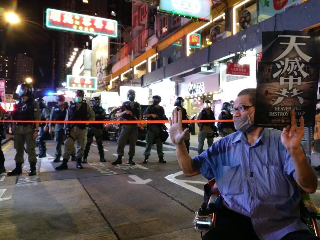 5月10日母親節,一位男士將《大紀元時報》香港版的「天滅中共」連同「五大訴求」的手勢一起向站在他附近的警察舉起,表達「天滅中共」和「五大訴求」密不可分的理念。(大紀元資料圖片)