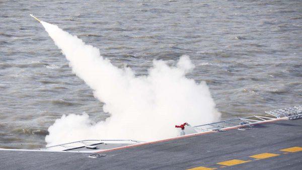 圖為中共遼寧號航母在渤海軍演中發射導彈。(STR/AFP/Getty Images)