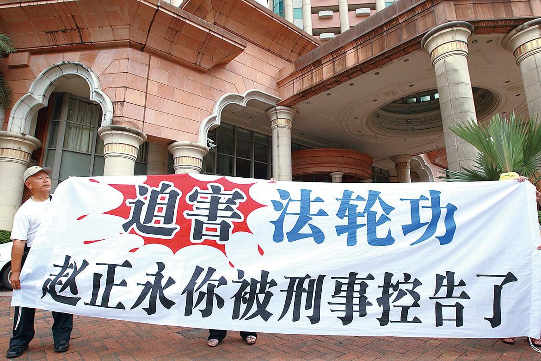 2010年9月14日,到訪台灣的陝西省代省長趙正永走出亞太會館時,受到十幾位法輪功學員遞訴狀和舉橫幅抗議。(宋碧龍/大紀元)