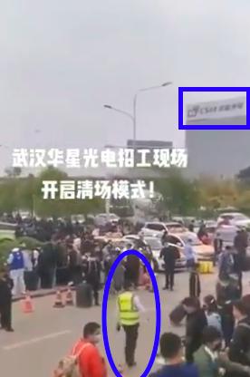 影片背景是武漢華星光電的大樓。圖中橢圓形藍框裏的人,就是疑似工作人員。(影片截圖)