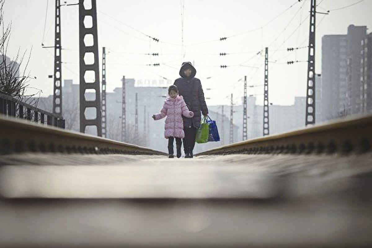 中國一半以上家庭,已在破產邊緣。財經專家認為,這並不是危言聳聽。圖為:大陸某市一家中國家庭母女行走在街道上。(Getty Images)