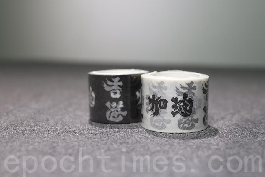 黑白分明的「香港加油」膠紙,蘊含著「黑白是良知」的意義。(陳仲明/大紀元)