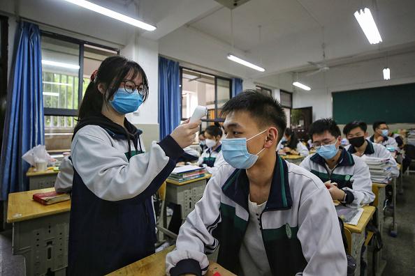 2020年5月,武漢已復課。圖為一中學,上課前學生們在測量體溫。(STR/AFP via Getty Images)