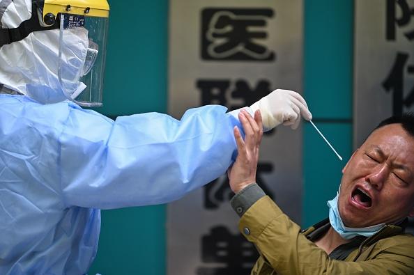 圖為2020年4月,武漢一男士在做中共病毒測試唾液取樣時的表情反應。(HECTOR RETAMAL/AFP via Getty Images)