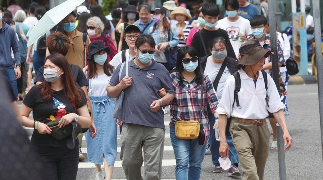 美媒記者秦穎表示台灣有效控制疫情,民眾生活如常。圖為5月3日天氣熱,民眾戴墨鏡及口罩出遊。(中央社)