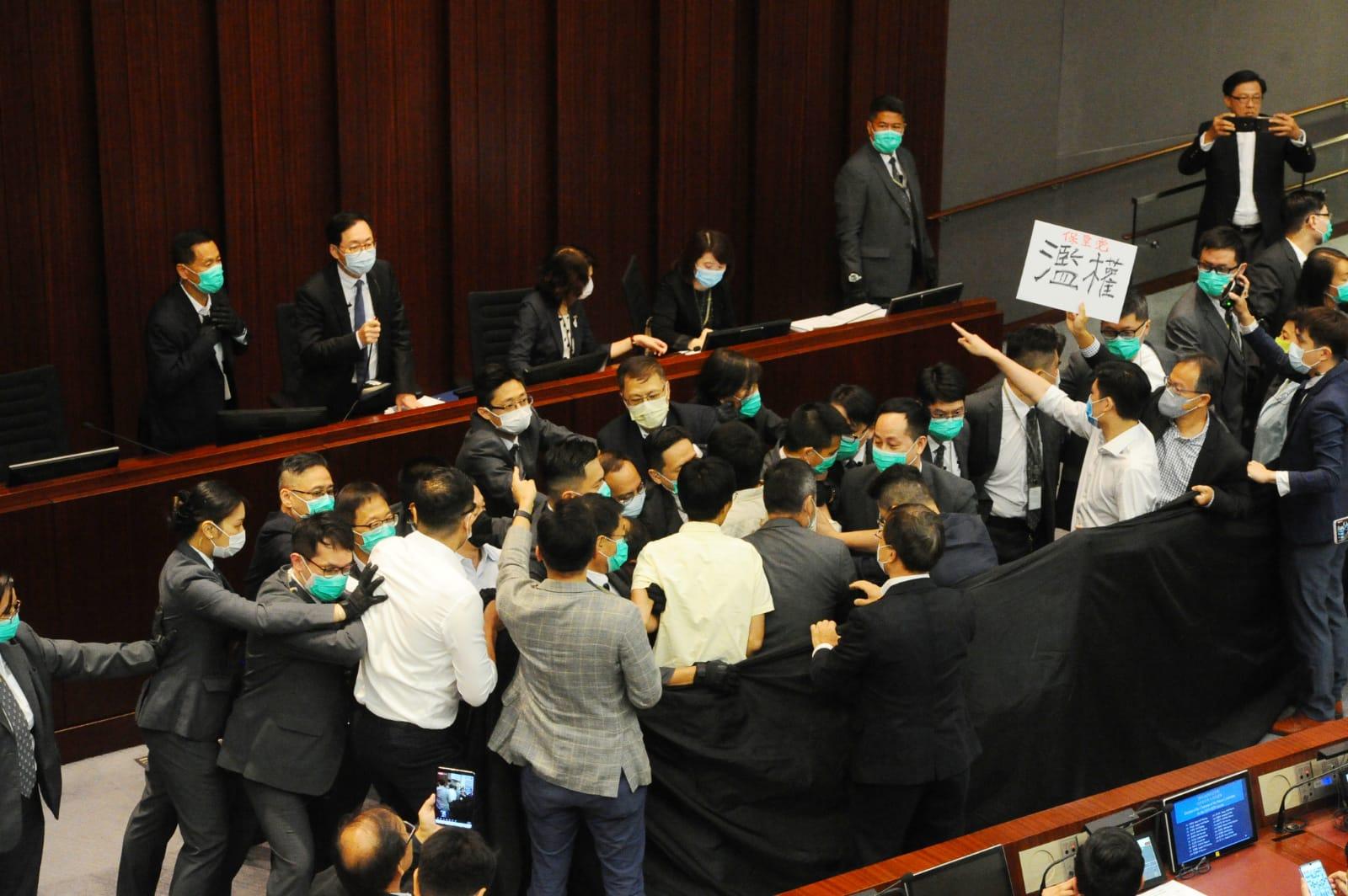 多名民主派議員也進入議事廳站在主席台前的保安人員旁邊,並打出標語「陳健波濫權」,同時質問陳健波,指其非法霸佔主席台,並拉起黑布抗議。(宋碧龍 / 大紀元)