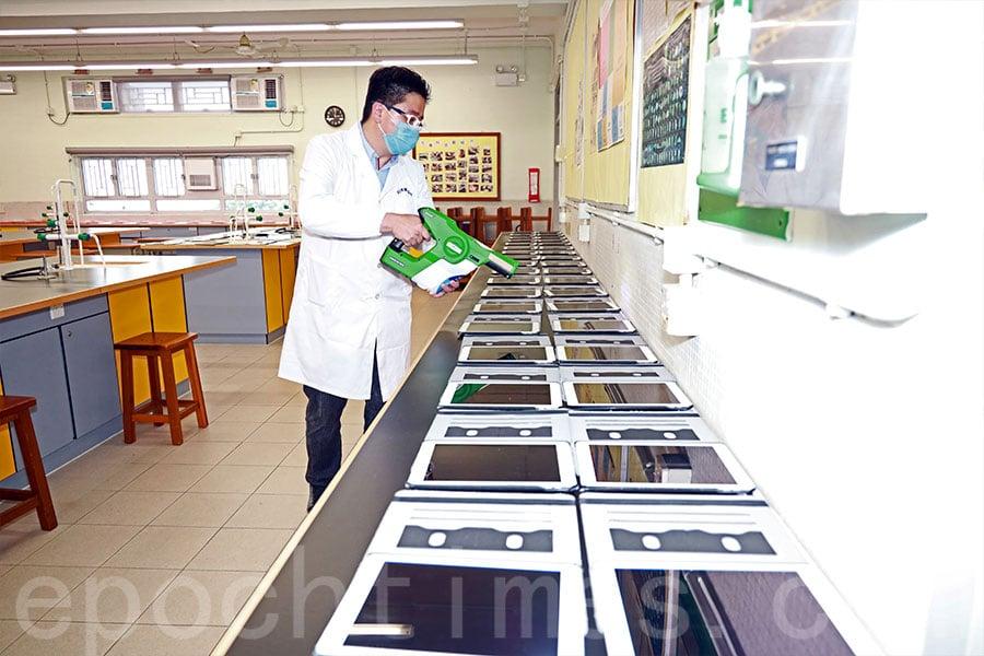 工作人員為學校的iPad噴灑殺菌塗層。(陳仲明/大紀元)