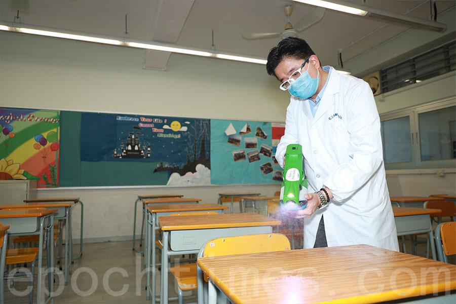 工作人員為課室的桌椅噴灑殺菌塗層。(陳仲明/大紀元)