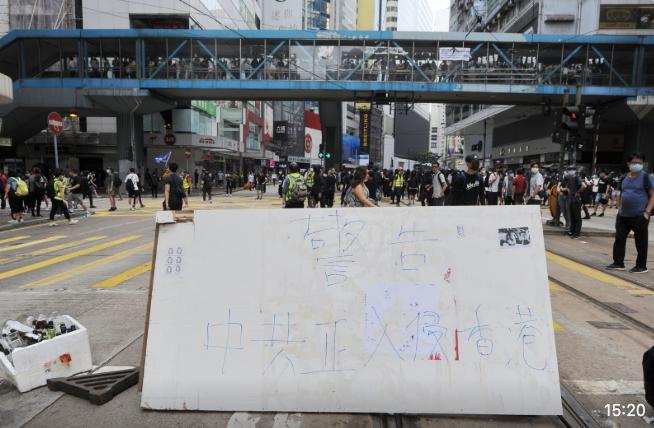 抗爭者在灣仔軒尼詩道立牌,「警告:中共正入侵香港」。(宋碧龍/大紀元)