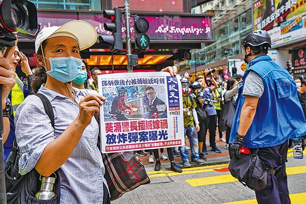 (左)2020年5月24日,反「港版國安法」遊行。在銅鑼灣有人拿大紀元報紙給警察看。(唐虞/大紀元)