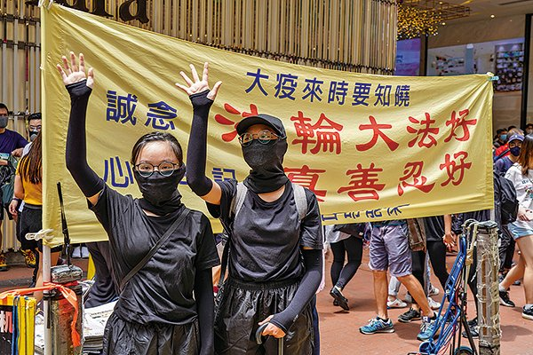 (上)2020年5月24日,反「港版國安法」遊行。在銅鑼灣港人在法輪大法橫幅前舉手表達五大訴求。(唐虞/大紀元)
