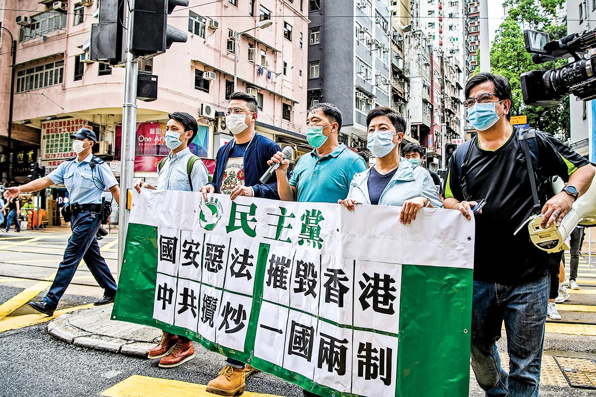 香港民主抗議人士5月22日拿著標語牌,抗議中共對香港強加國安法。(AFP)