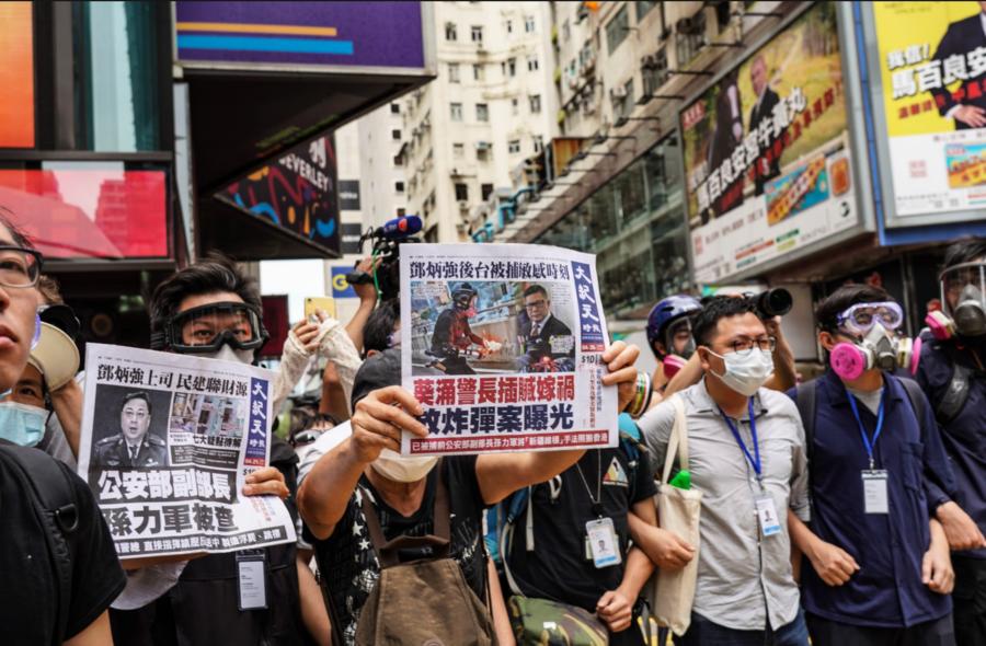【組圖】【5.24銅鑼灣遊行】 有市民向警察展示《大紀元時報》頭版鄧炳強  年輕人被拘捕