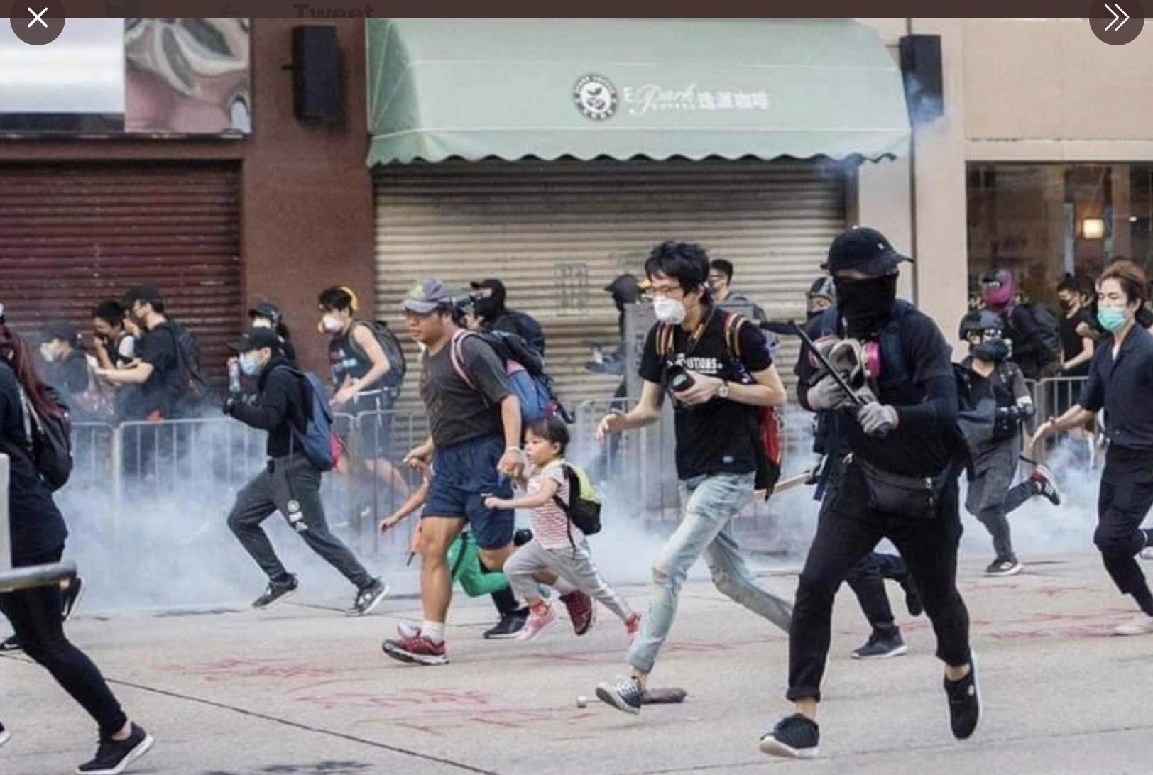 一名父親帶著兩個孩子在催淚彈煙霧中奔跑的圖片,在網絡上感動很多人。(網路截圖)