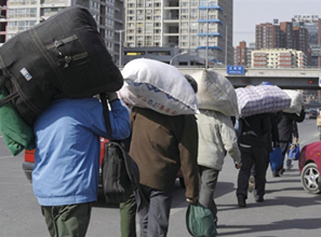 目前大陸社會信心崩潰,令中共營造的政權合法性難以維繫。圖為民工扛著行李走在北京街頭。(法新社)